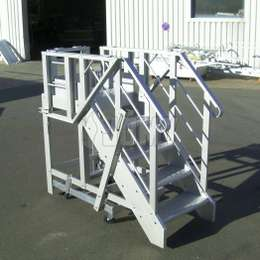 Mobile aluminium industrial platform and stairs with collapsible guardrails.